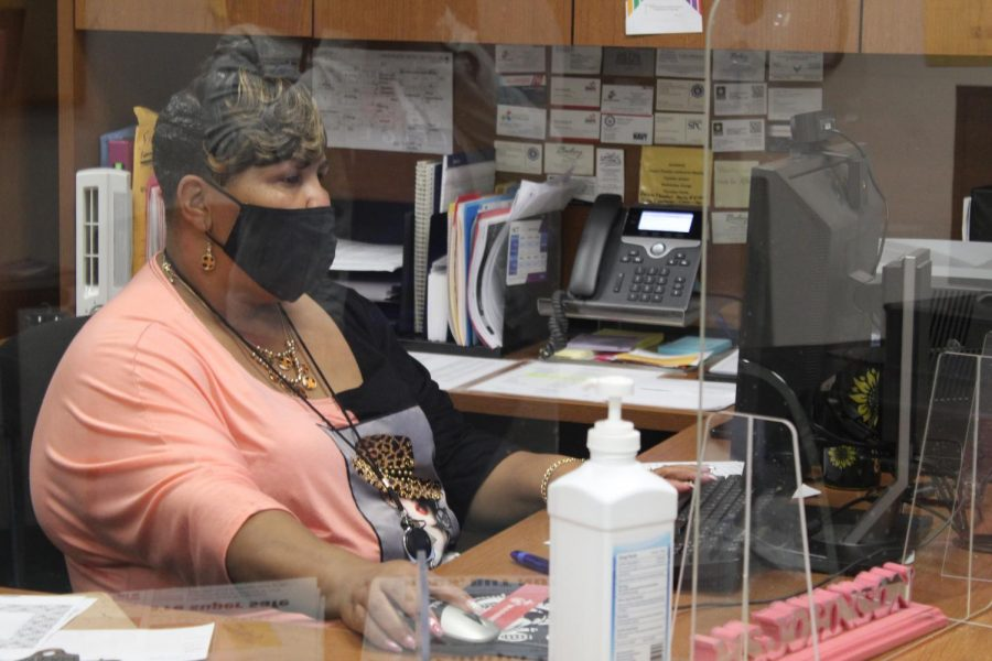 """Guidance  secretary Dricilla  Johnson works  at her desk  behind Plexiglas  in the guidance  office on Feb.  3. """"I came to  Lakewood to  better my career  options and  my education,""""   Johnson said."""