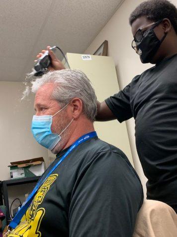 Freshman Adrian Lovett shaves the hair off teacher Michael Dolhancryk 's head in November in VE specialist Emily Cipolla's office.
