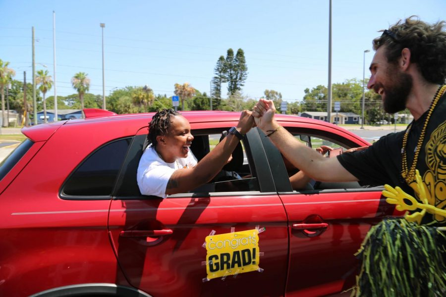 Lakewood graduate Jo Shauntye Thomas, left, fist bumbs history teacher Brandon Vaughan as she is driven through the Lakewood cap and gown distribution in May of 2020.