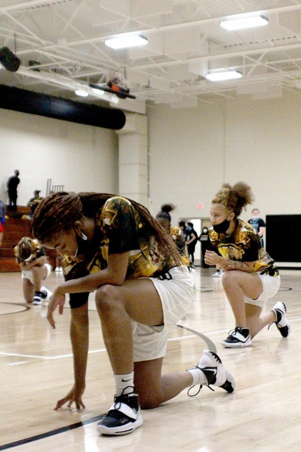 Senior Nilah Coleman kneels with her team for the  national anthem Feb.12 in the Lakewood High gym.