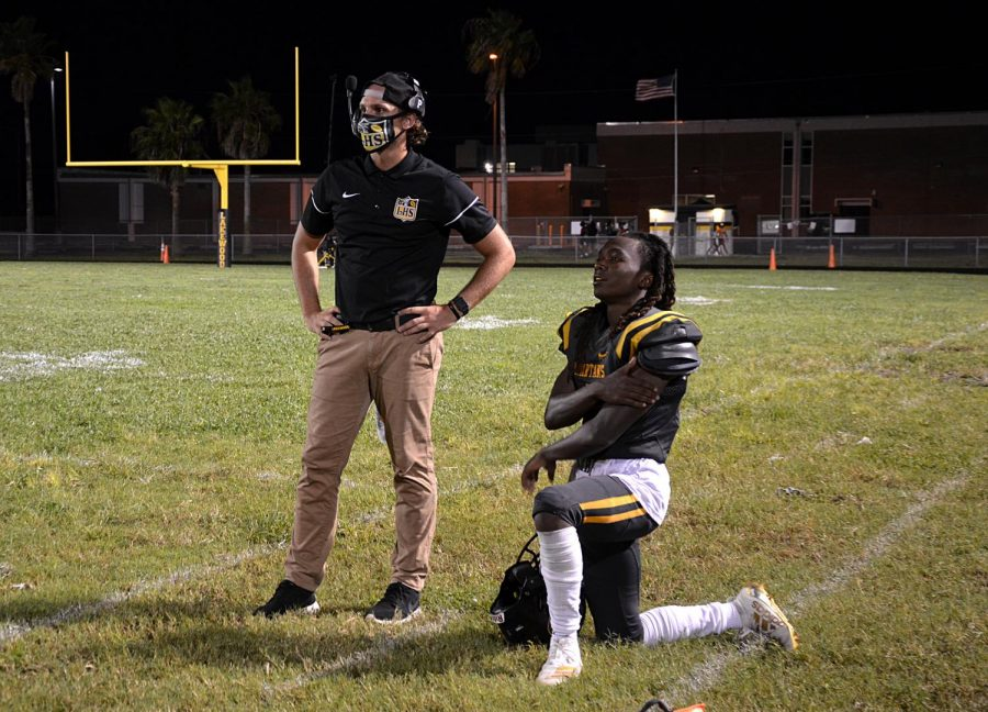 Defensive coach Philip Muszynski and junior Camari Berry watch the Gibbs game from the  sidelines on Sept. 11.