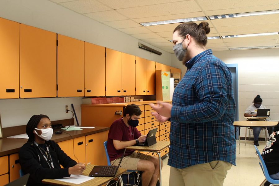 """New English  teacher Chris  Mosher talks to  junior Sincere  Robinson about  classwork  on Jan. 26 at  Lakewood High  School. """"It is  going awesome;  the kids are  great,"""" Mosher  said."""
