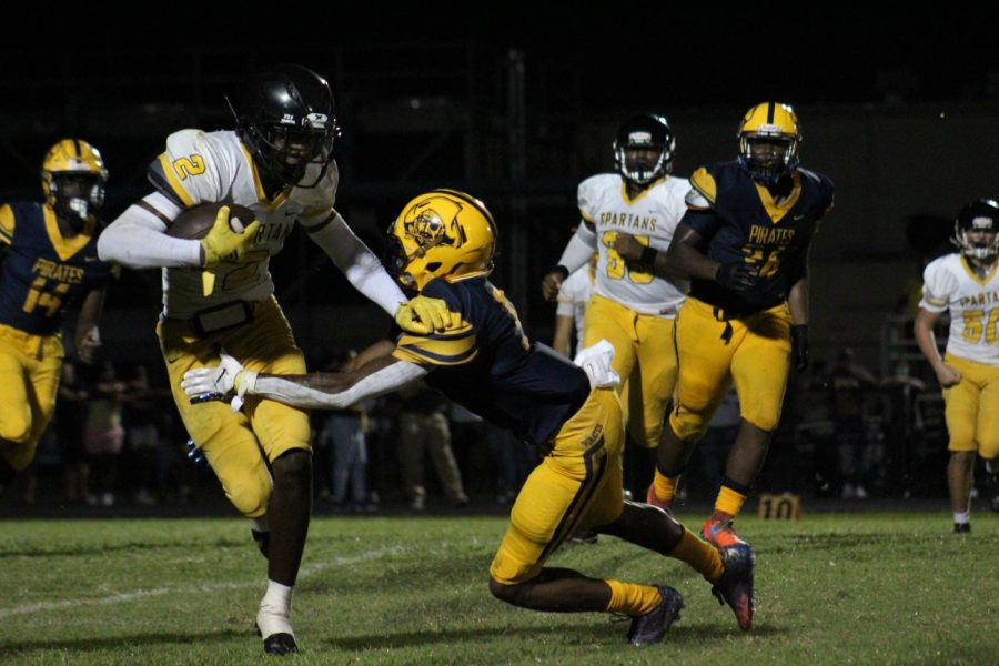 Senior Terrell Crosby runs the ball against a Boca Ciega High School defender at the game on Aug. 26. The Spartans beat the Pirates 27-12.