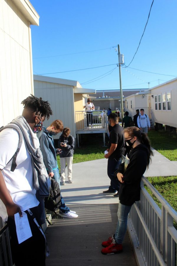 Students wait outside of portable 11 for their teacher on the first day of school on  Aug. 11. This school year masks are optional. I dont want to get sick and dont want others to get sick either, said junior Hayley McCormack.