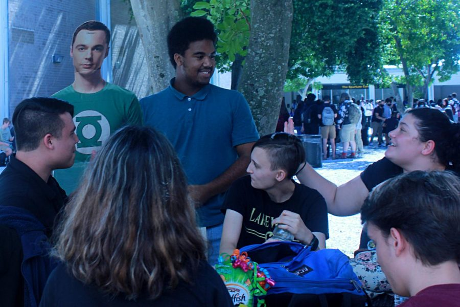 Senior Sebastian Brown shows off a cardboard cutout of Sheldon from Big Bang Theory to seniors Jordan Alcira, Emma Ash, Jordan Thompson, Kasey Hovey and Zachary Oetinger in the courtyard during lunch on Aug 16. Brown got the cutout after network administrator Christopher Borg threw it away.