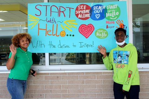 Junior Falicity Ozuna and senior Cameron Copeland pose in front of the Start with Hello week poster on Sept. 22 in front of the cafeteria. The poster was created by the SAVE Club, which organized the week of activities.
