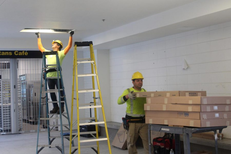 Constructions workers install new light fixtures in the ceiling near the Spartan Cafe by the Hub.