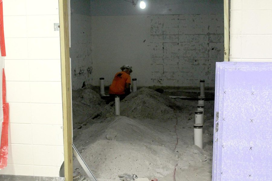 A worker guts the mens and womens bathrooms in the auditorium lobby, before installing new toilets, sinks and fixtures.