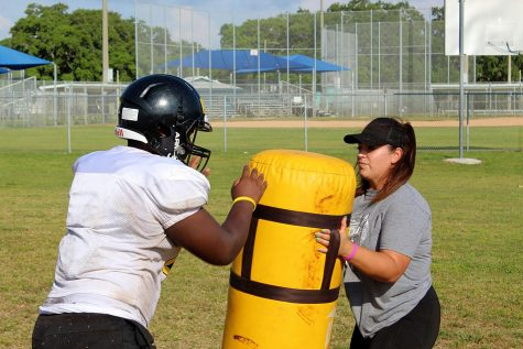 Coach Melia Garcia works with a player from the offensive line on a blocking drill in May on the Lakewood High School practice field.