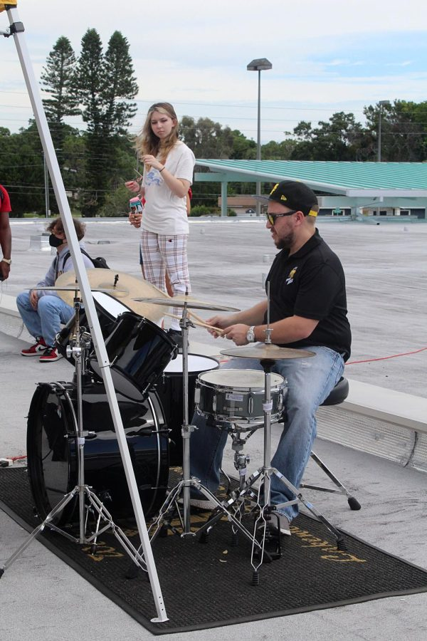Music teacher Jacob Merrett plays the drums at the roof top concert on Oct. 6.