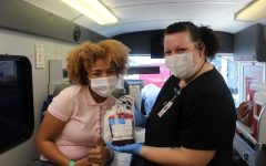 Junior Falicity Ozuna poses with nurse Jordan Lewis with her pint of blood on Sept. 21. Many students will donate blood because to help a close friend or family memeber. My cousin has sickle cell so thats why Im donating. It feels great, Ozuna said.